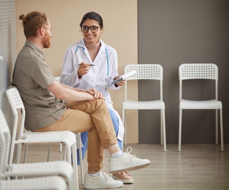 Young nurse in eyeglasses smiling and talking to patient while they sitting on chairs in corridor of hospital