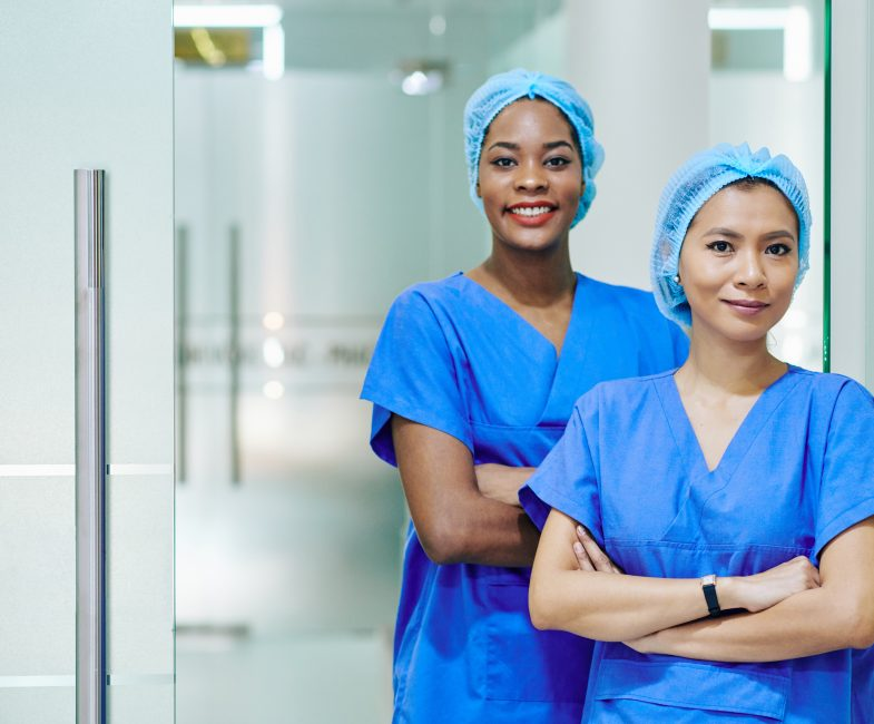 Smiling pretty multi-ethnic medical nurses in scrubs and disposable caps standing in hospital corridor